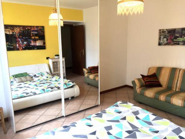 Camera matrimoniale con divano e grande specchio