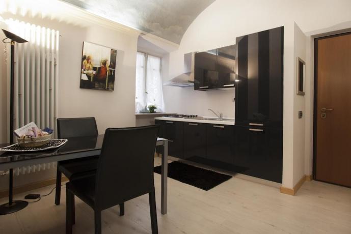 Camera con angolo cucina e salotto arredati