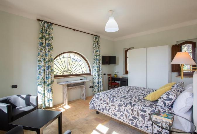 Camera con piccolo soggiorno e scrivania
