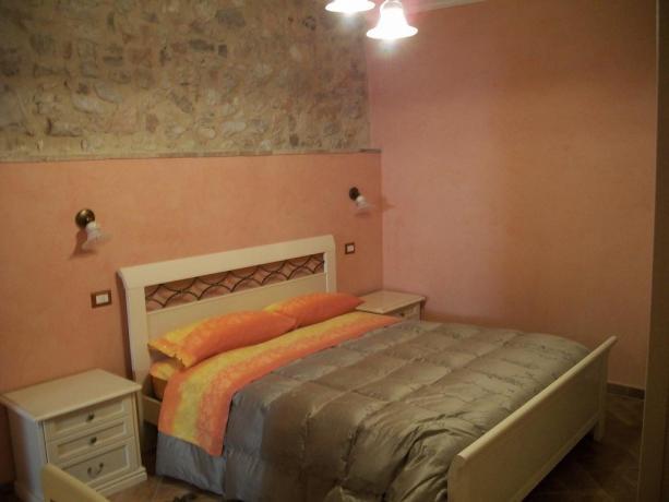 Camera matrimoniale con parete in pietra
