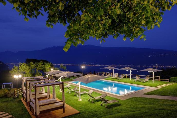 Piscina notturna illuminata con panorama Lago Garda
