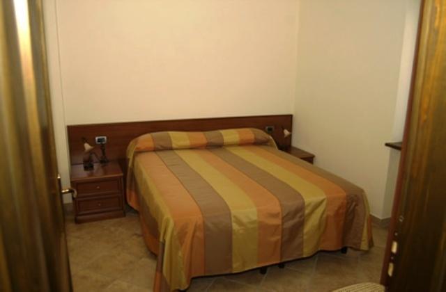 Camera con letto matrimoniale in arredamento rustico