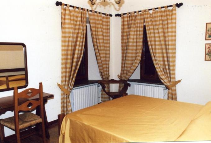 Camera con Termosifone, Tavolino, Sedia e Specchio