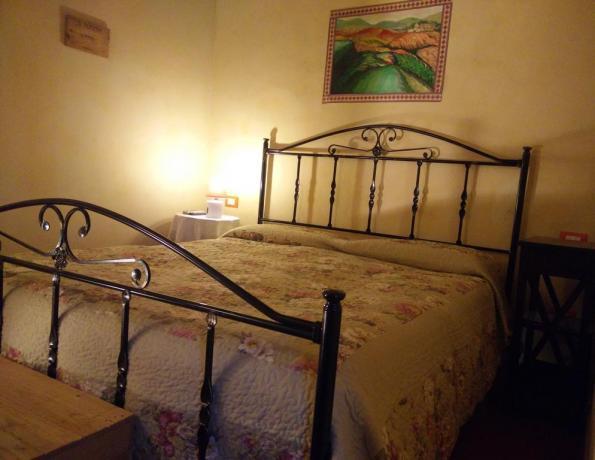 Camere con letti in ferro battuto nel Chianti