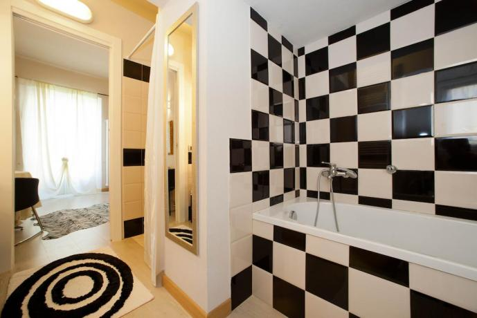 Camera con grande bagno arredato con vasca