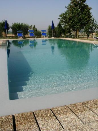 piscina con sdraio in casale a cortona
