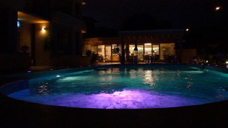 Piscina esterna di notte, residence nel Conero
